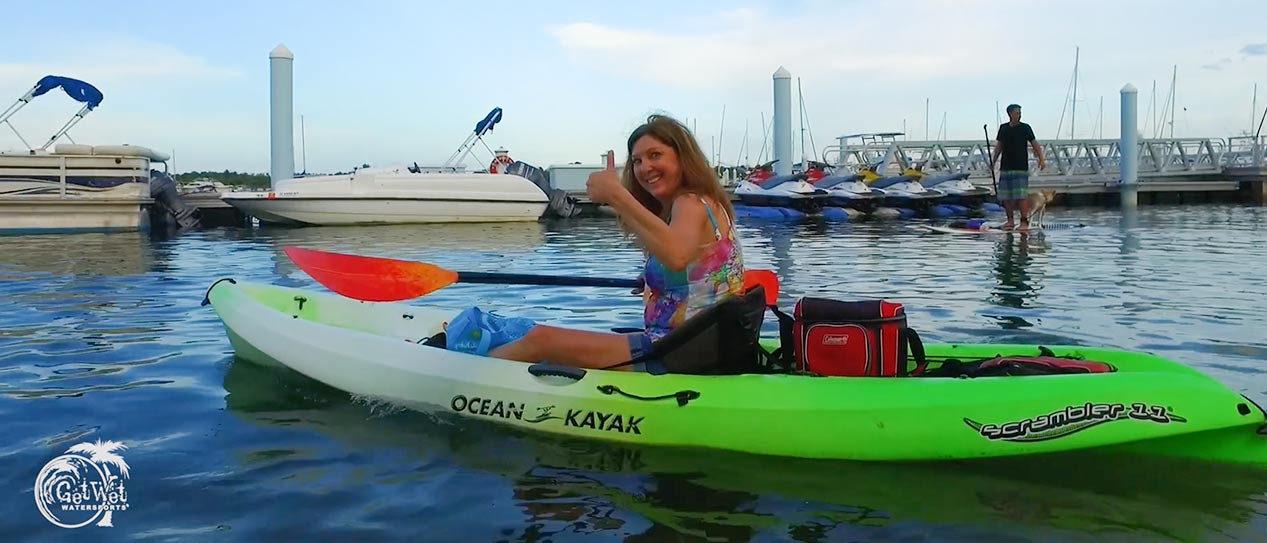 Girl giving thumbs up in green kayak